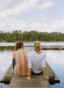 Young couple sitting on jetty --- Image by © Royalty-Free/Corbis