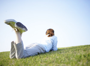 Young Woman Lying on Stomach on Grass --- Image by © Royalty-Free/Corbis