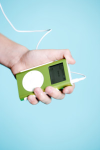 A hand holds a lime-green Apple iPod portable digital music player --- Image by © Royalty-Free/Corbis