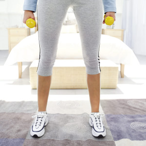 Woman Standing with Dumbbells --- Image by © Royalty-Free/Corbis